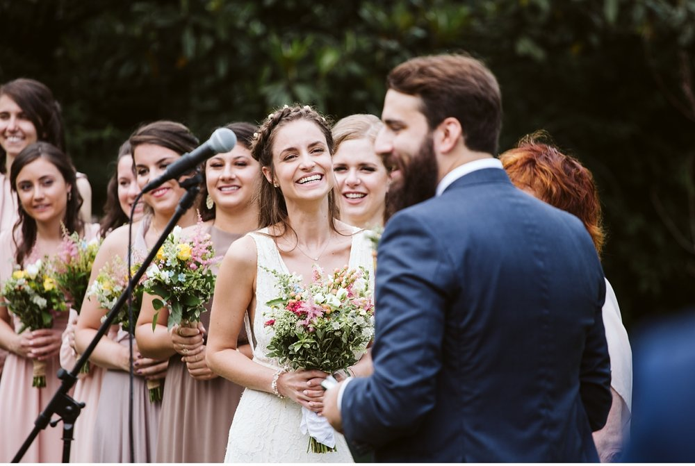 Bride laughing during ceremony at outdoor wedding
