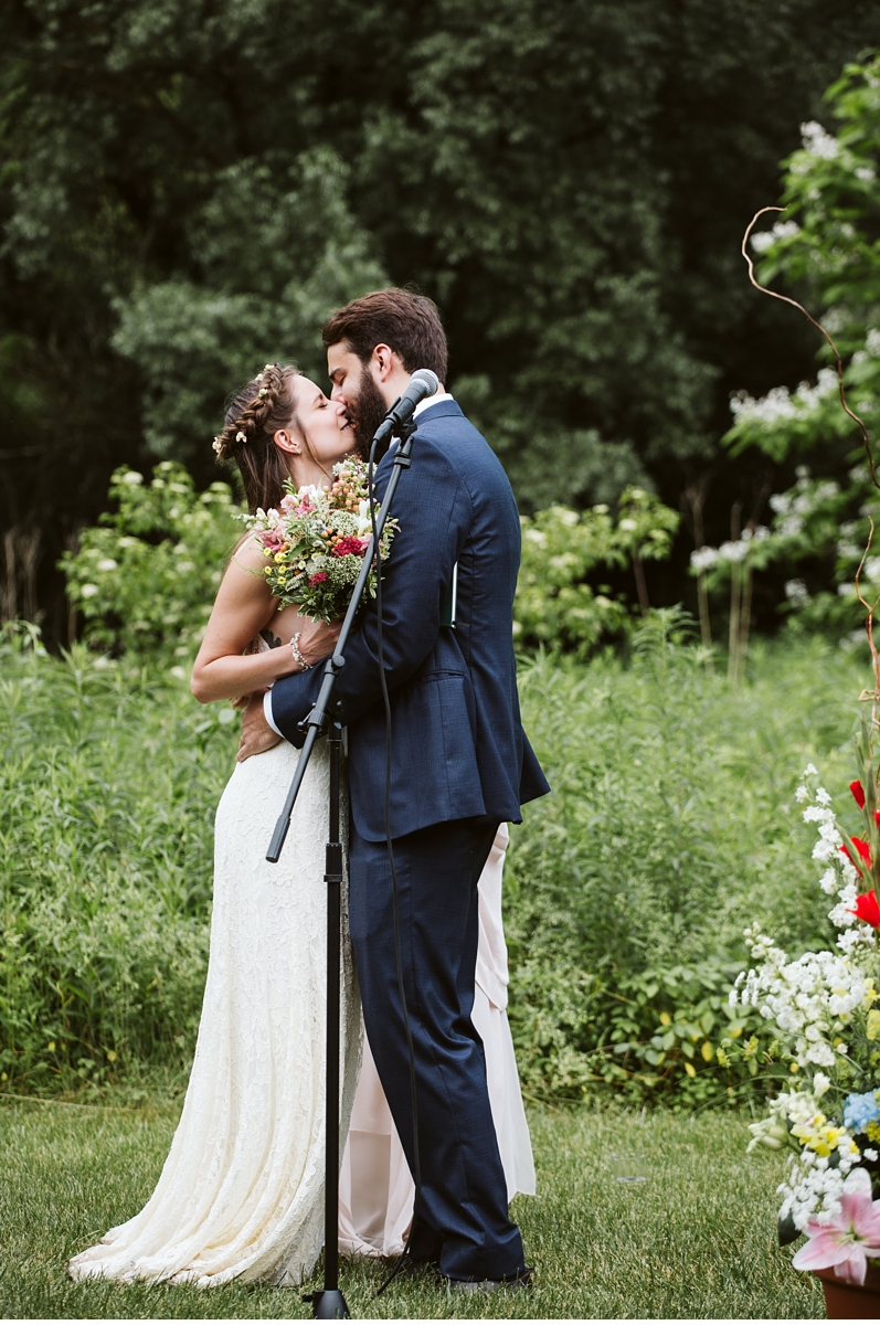 Bride and groom first kiss at Willowwood Arboretum wedding