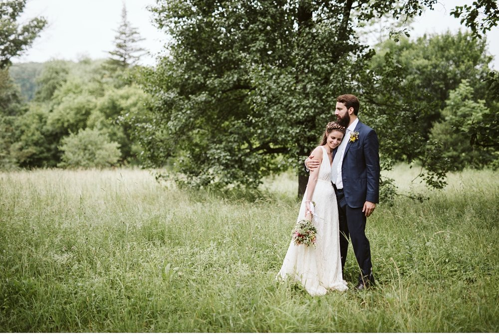 Bride leaning head on grooms chest in field during summer wedding