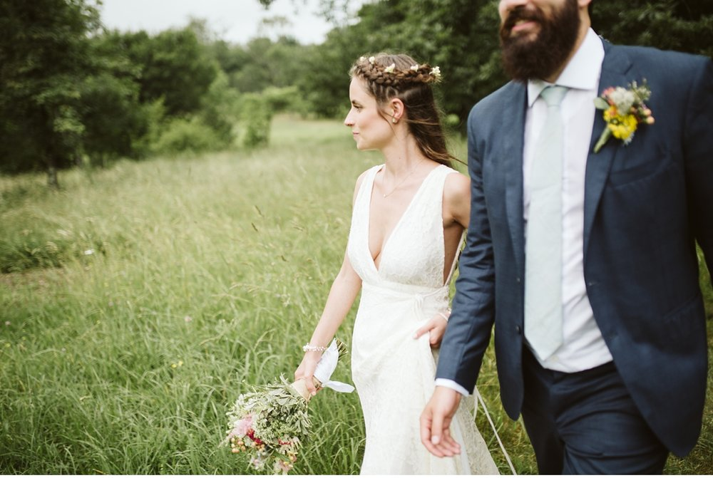 Candid of bride and groom walking through a field at Willowwood Arboretum