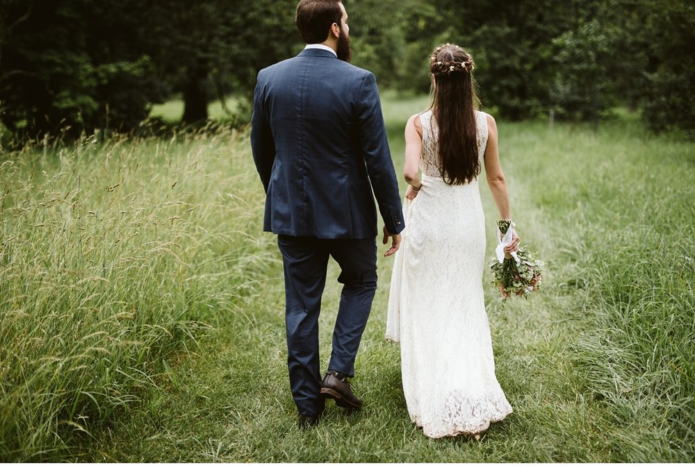 Bride and groom walking down grassy path