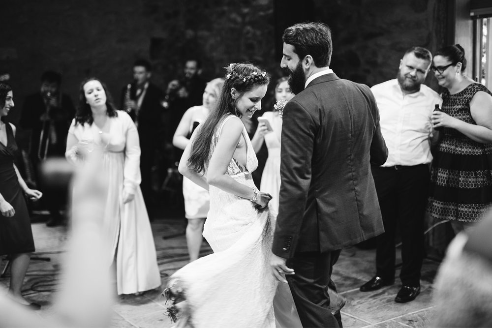 Bride and groom dancing in stone barn