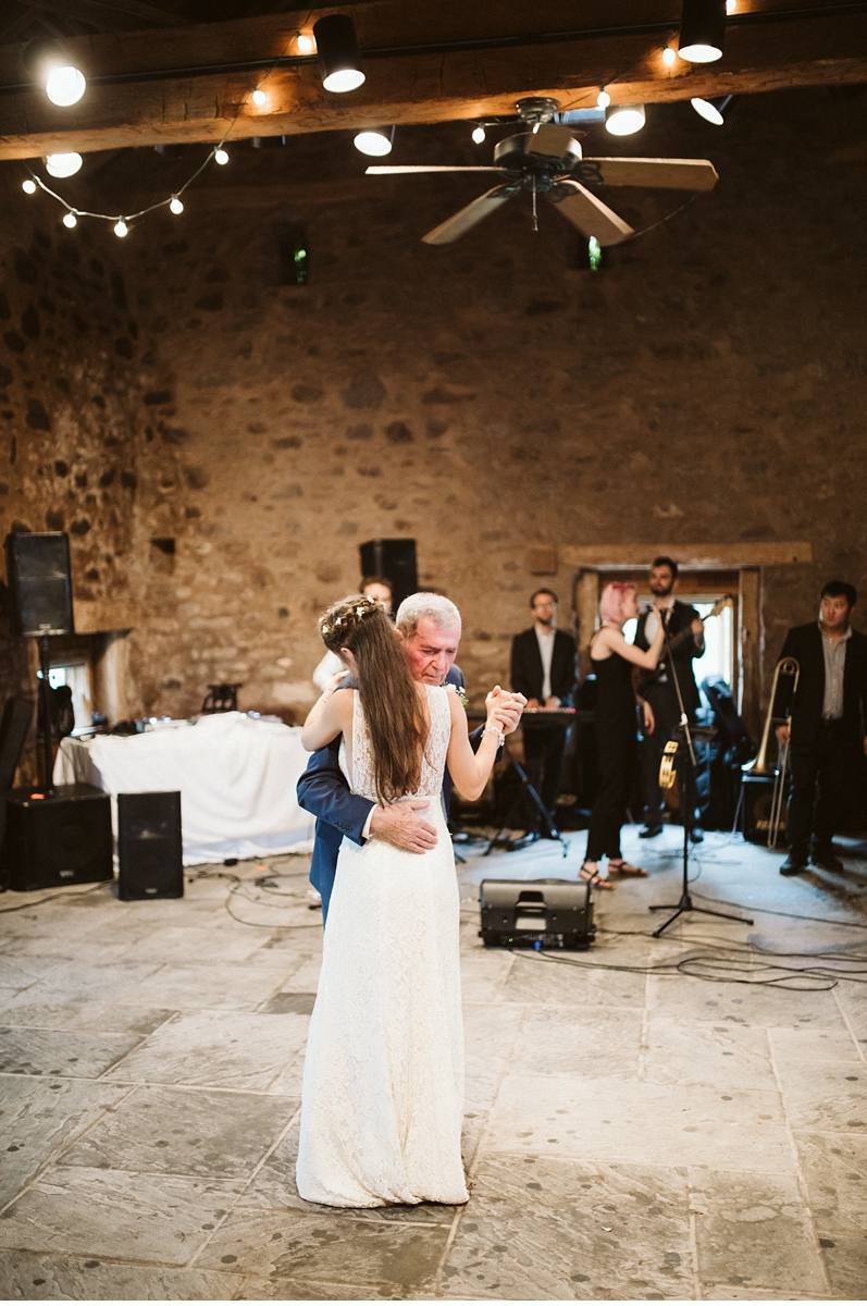 Bride hugging grandfather in stone barn at Willowwood Arboretum