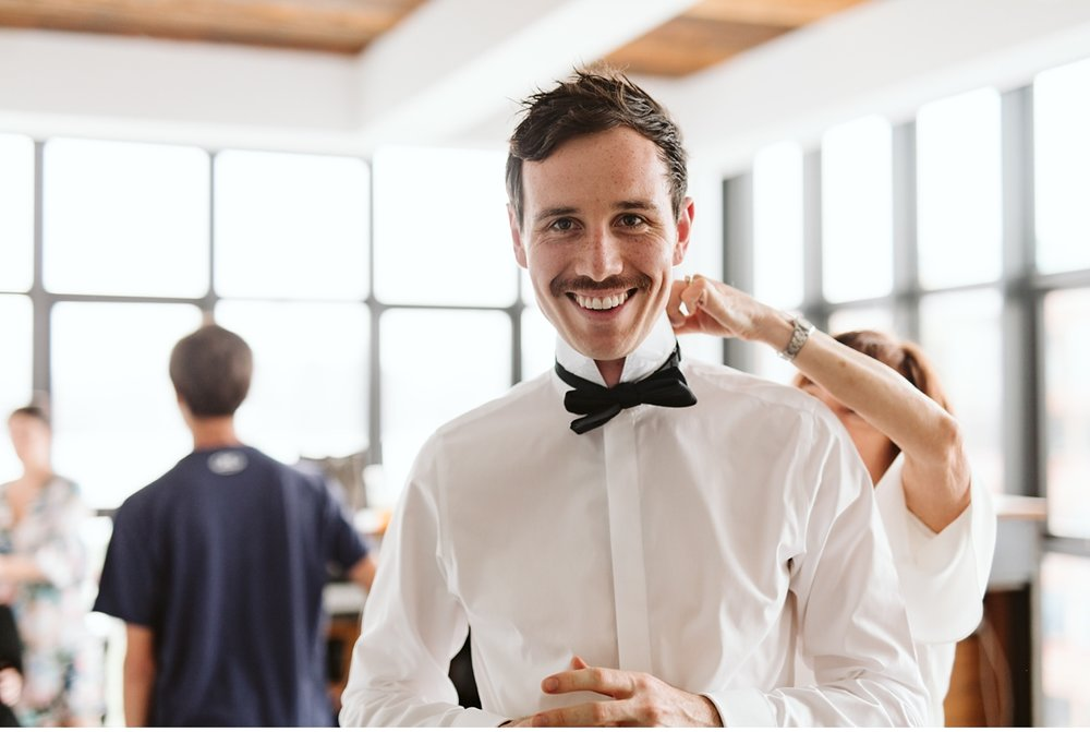 groom laughing while being helped with his bow tie