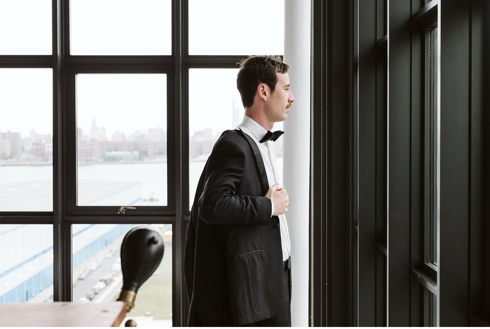 Groom putting on his jacket in front of large industrial window