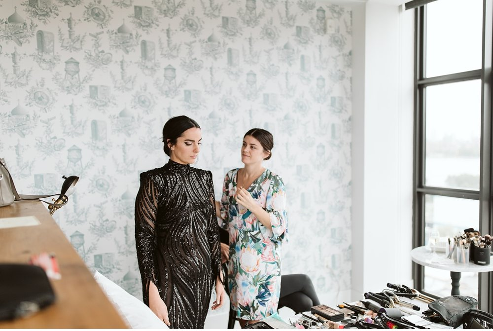 Friend helping bride into non-traditional black wedding dress at the Wythe Hotel