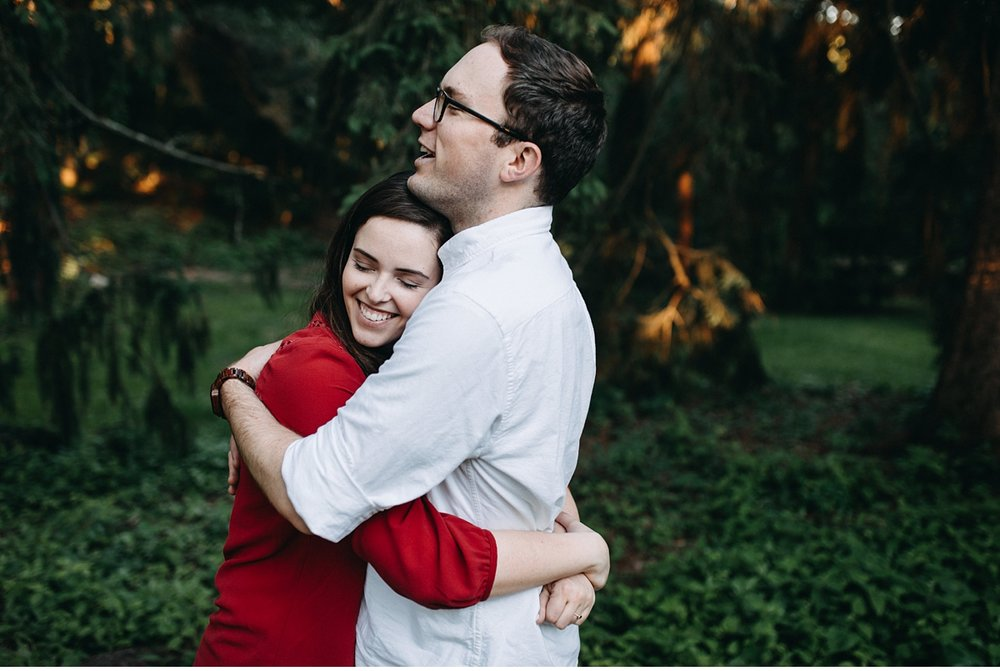 couple hugging surrounded by pine trees in the Arnold Arboretum