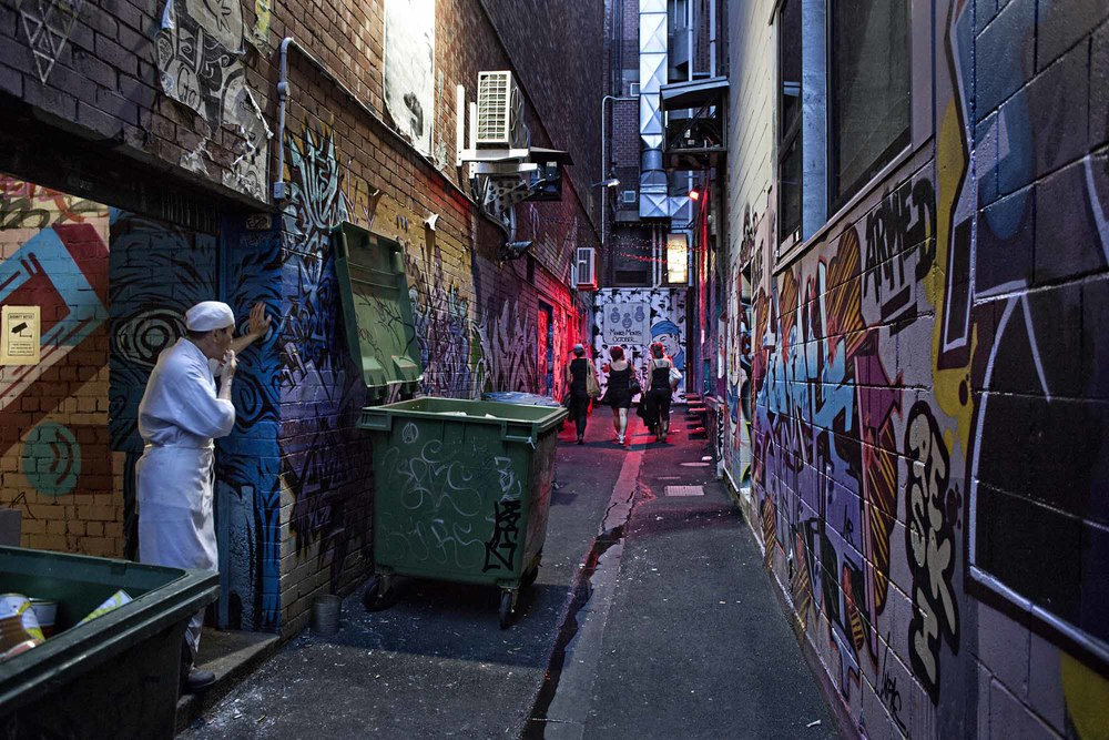 Croft Alley. Chef taking a smoko break watches club goers on their way to The Croft Institute, a bar and nightclub tucked down a winding Chinatown alley