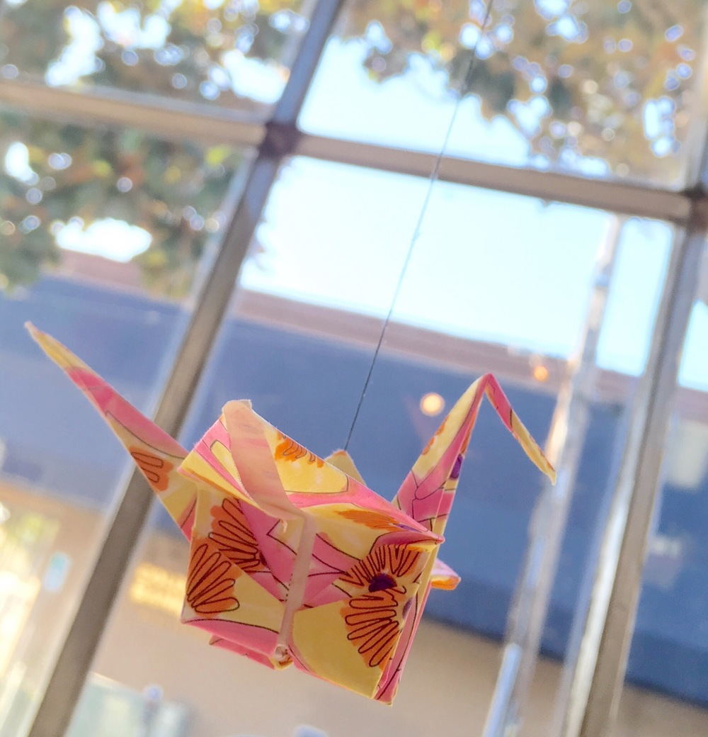 Paper cranes in variety of colors in the window.