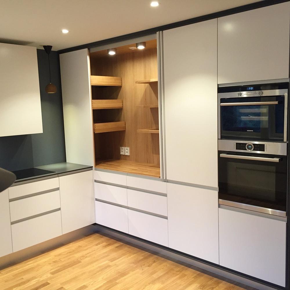 Kjøkkenet med åpne dører til grovkjøkkenet.   Grovkjøkkenet gir mange muligheter for å jobbe med diverse elektriske kjøkkenredskaper med tanke på tilrettelagt stikk og lagring. Hele grovkjøkkenet vil skjules bak skapdører når det ikke er i bruk. Dette gjør arbeidet på kjøkkenet både praktisk og ryddig.