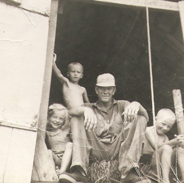 Edgar Cook, Nick's grandfather, sits with his children in a barn on the family farm. c. mid 1950s.