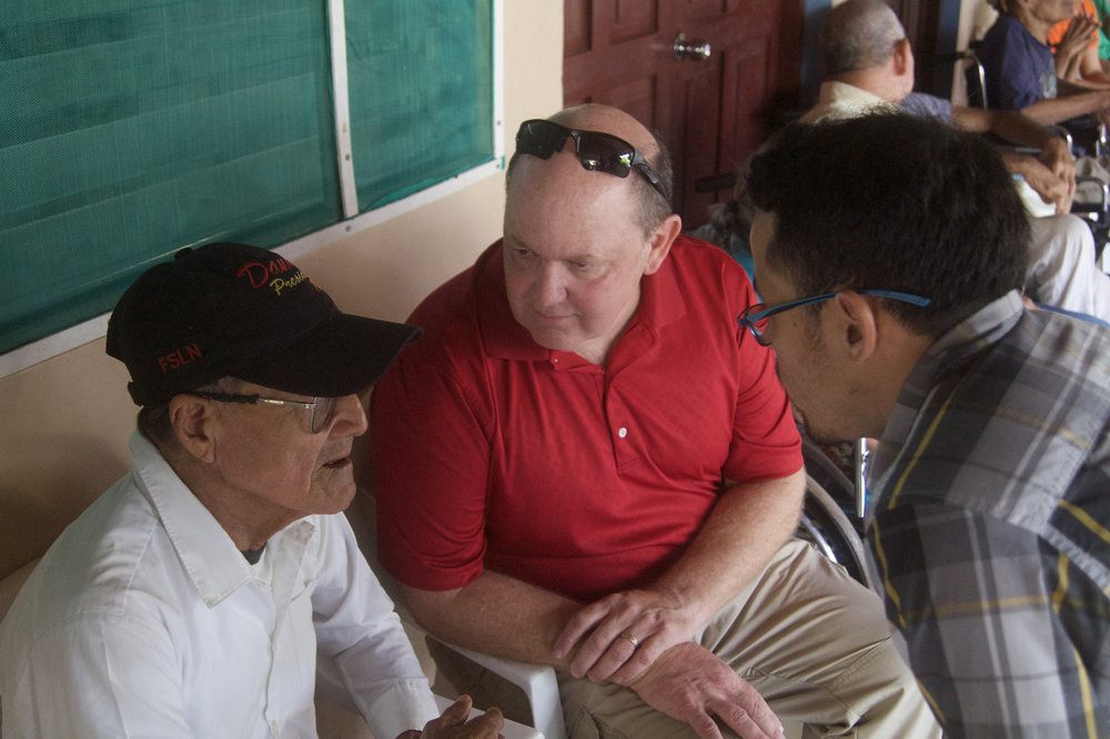 Matt Tveite, with the help of Reynaldo, speaks with a resident