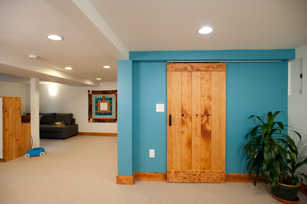 "The new barn door covers what used to be just an opening to the laundry room. Its warm wood against Sherwin Williams' ""Lakeshore"" blue make for a striking and welcoming view upon entering the basement from upstairs."