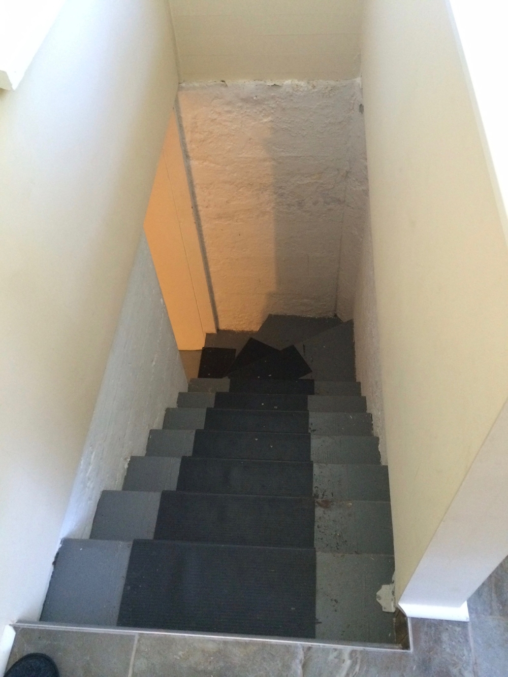 "BEFORE: Stairs too steep with poor headroom at bottom. No light fixture, and walls felt ""cold"" and dirty."