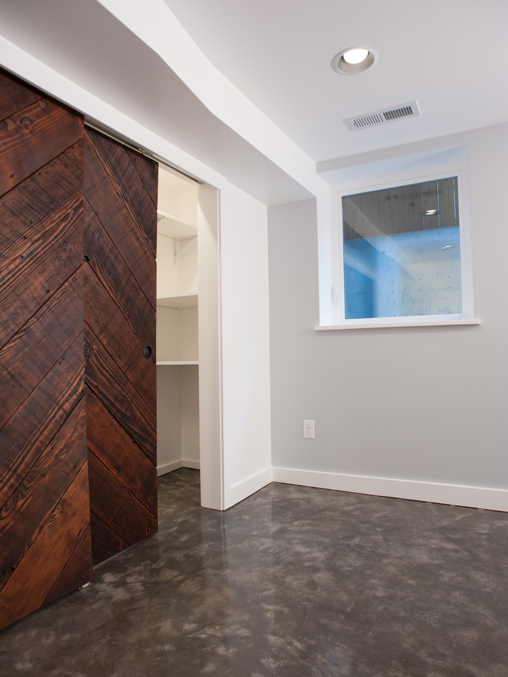 AFTER: All new finishes upon insulated walls, plus a new egress window make for a comfortable (and legal!) living space. Custom reclaimed-wood bypass closet doors and stained concrete floors are statements in an otherwise simple room.