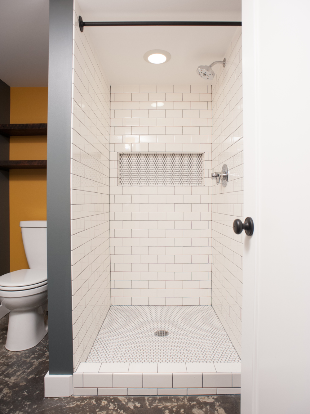 AFTER: Improved layout with tiled shower, modern fixtures, and custom steel-pipe towel bars.