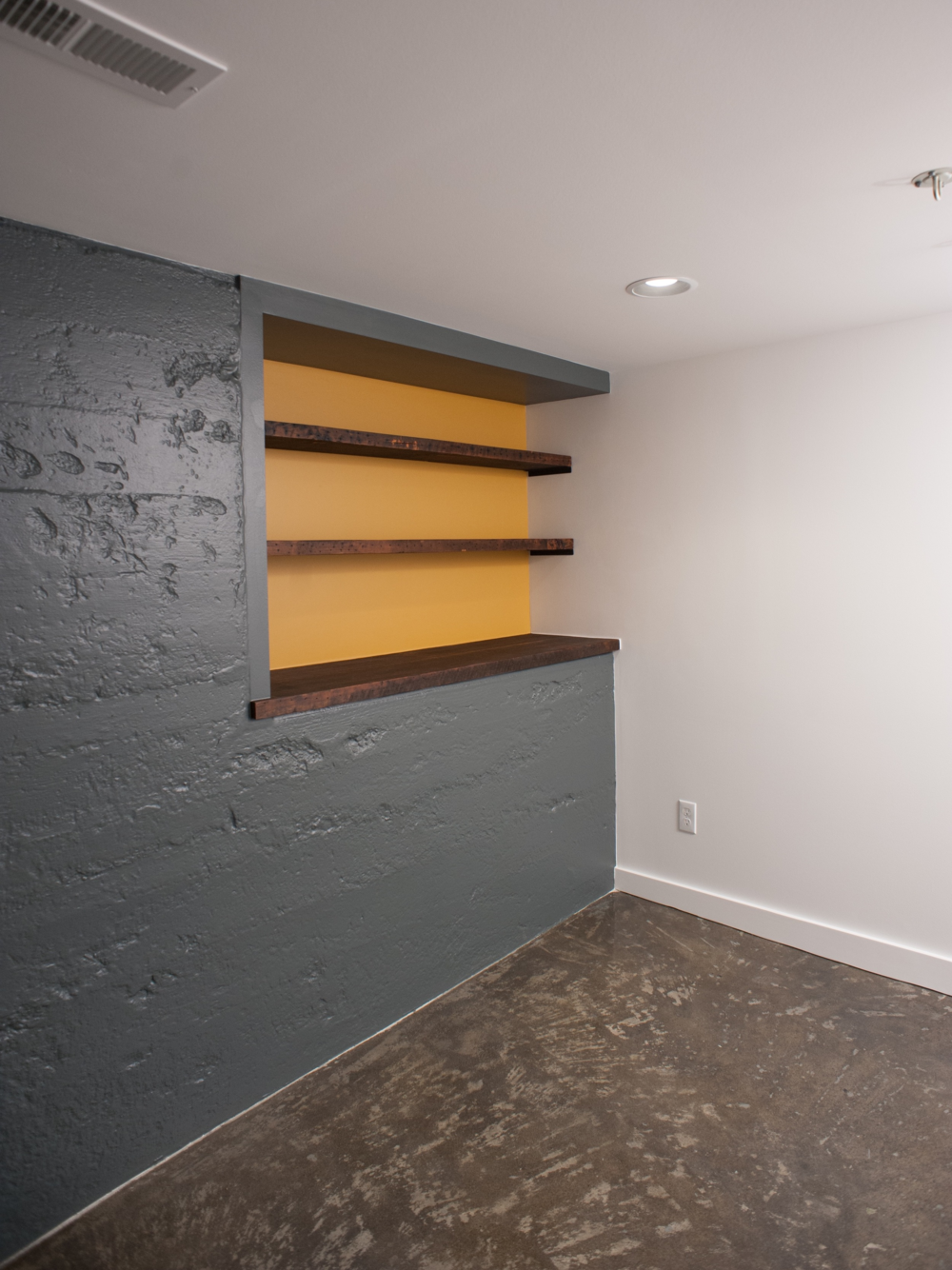 AFTER: Main room is now a living space with all new finishes, utility lines tucked away out of view, and a feature wall of painted concrete with a warm shelving nook. A separate laundry area was created in a previously unfinished part of the basement (not pictured).