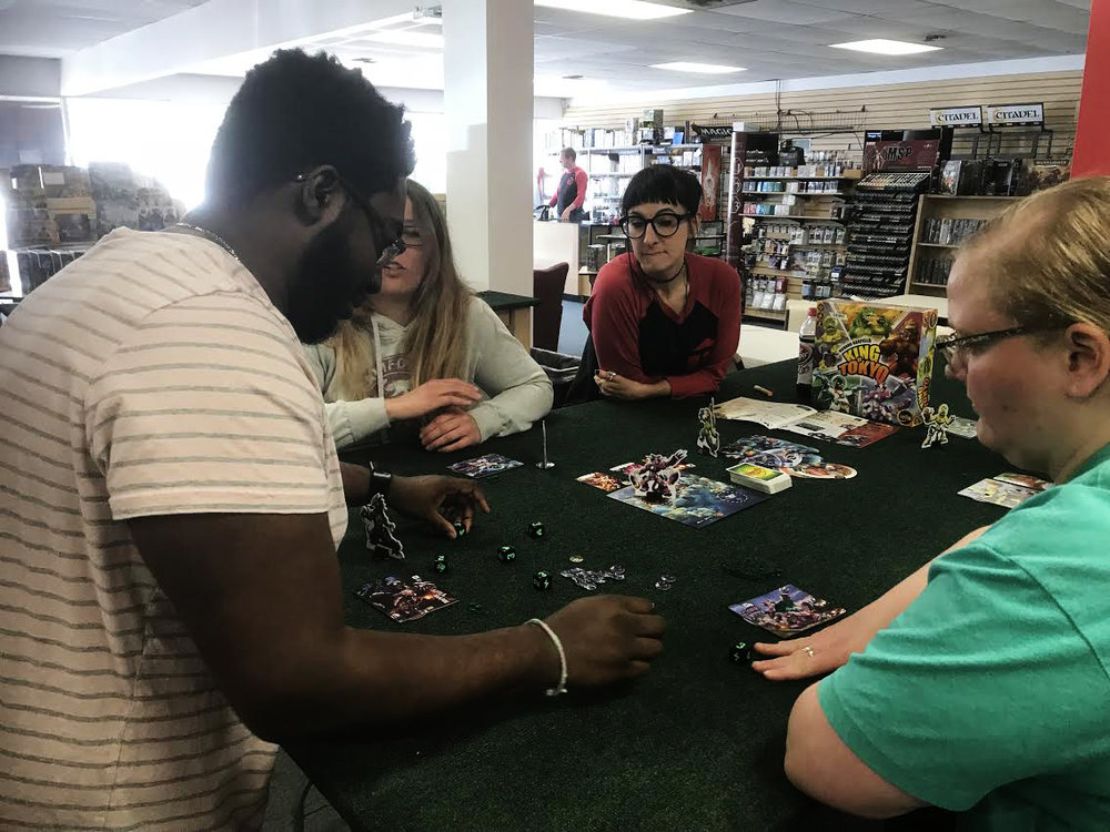 Devoted FLGS employee Jacinda teaches a group of three how to play one of our favorite games: King of Tokyo!