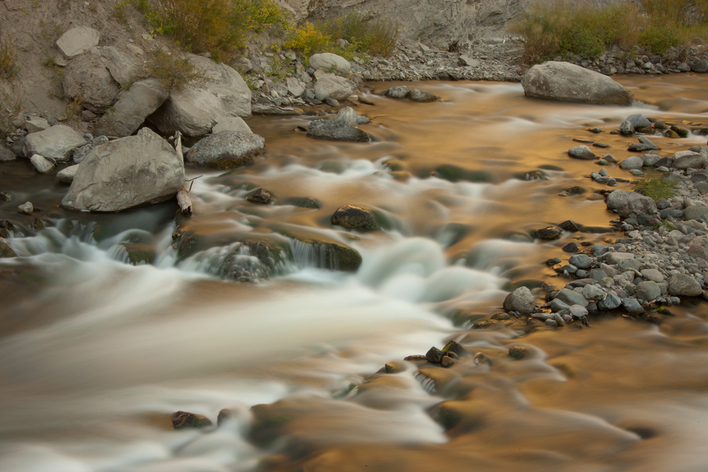 Gardiner River I walked up and down the road paralleling the river to find a spot where the late evening light striking the cliffs was reflected as gold water, and the 13 second exposure softened the rapids and ripples to a pleasing blur.