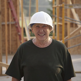 a happy self builder standing in front of a partially built wooden frame house wearing a safety helmet wearing a black t-shirt