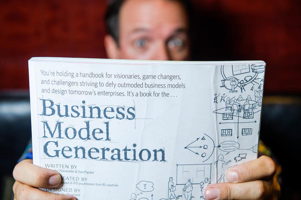 Entrepreneur John Andrews posing for portrait photo with a book