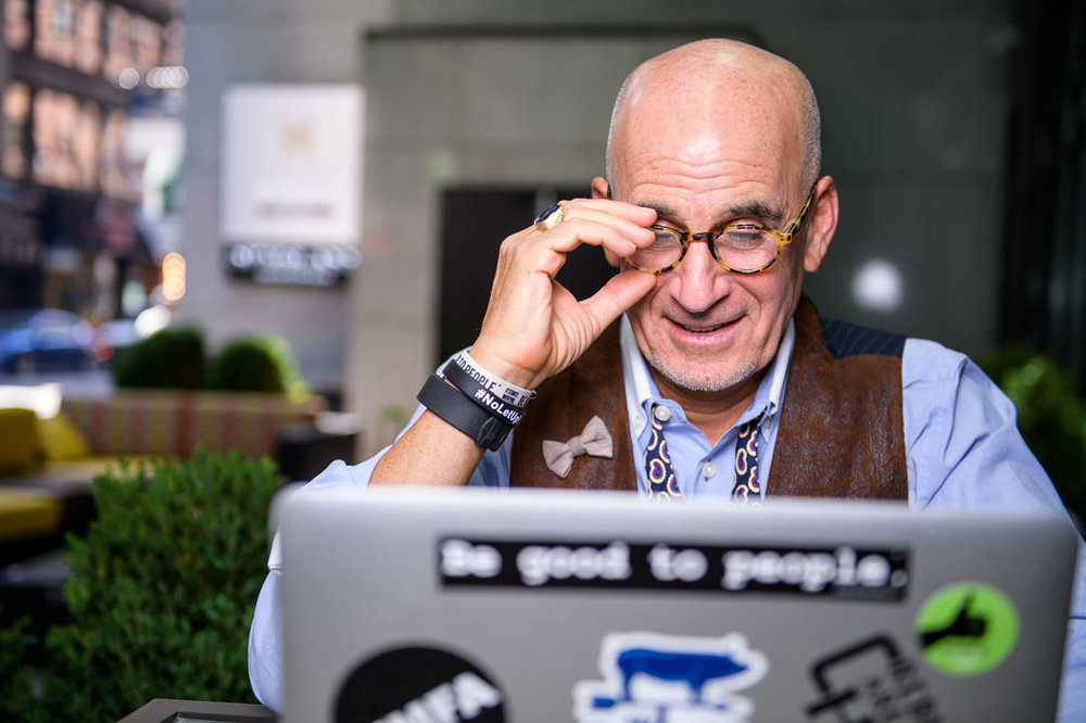 NYC Branded Lifestyle Portrait SpeakerAuthor Thought LEader Ted Rubin fixing glasses