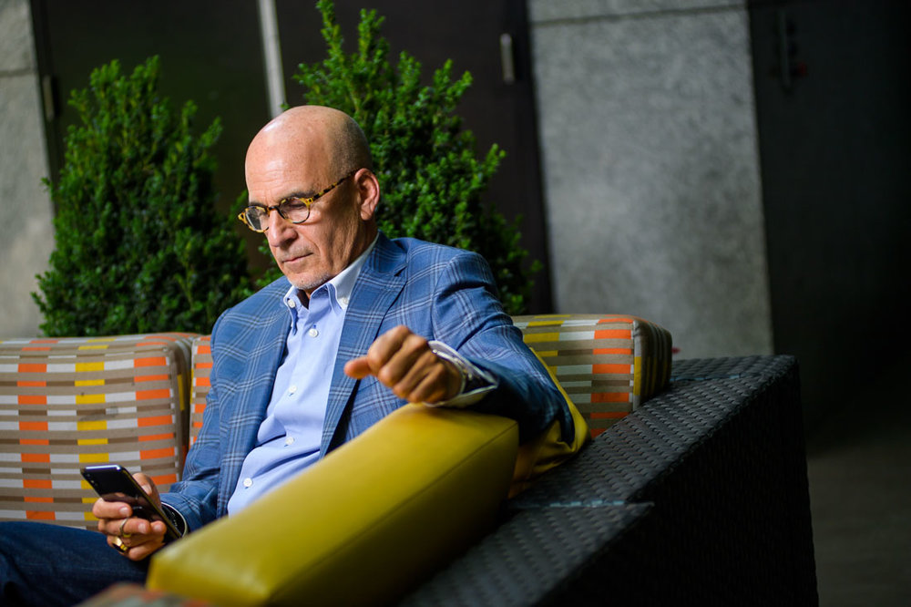 NYC Branded Lifestyle Portrait SpeakerAuthor Thought LEader Ted Rubin sitting and checking phone