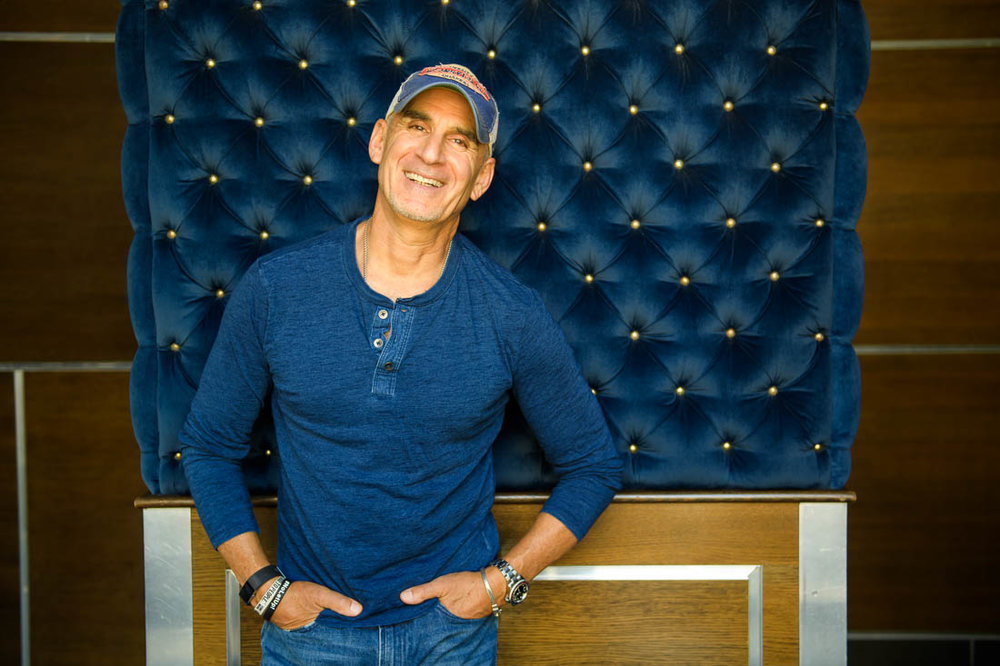 NYC Branded Lifestyle Portrait SpeakerAuthor Thought LEader Ted Rubin smiling against pillar