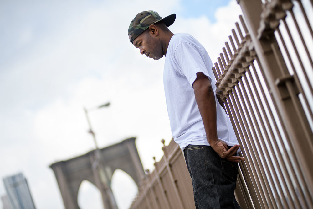 NYC Branded Lifestyle Portrait Podcaster G Moody Brooklyn Bridge looking down thinking