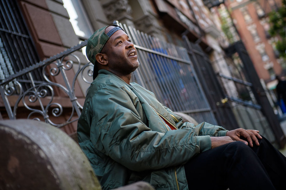 NYC Branded Lifestyle Portrait Podcaster G Moody stoop looking up and smiling