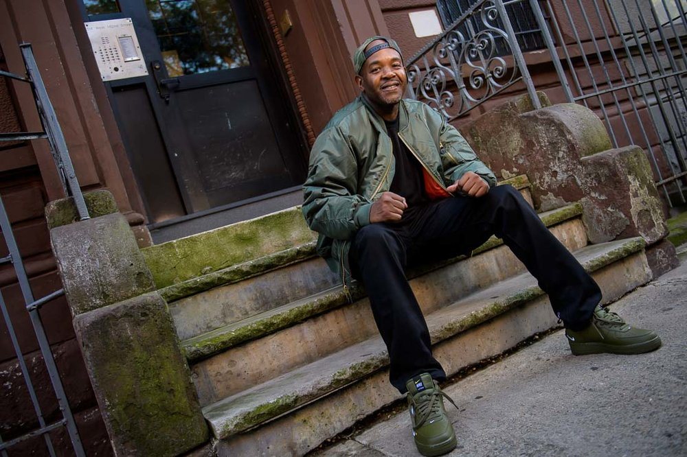 NYC Branded Lifestyle Portrait Podcaster G Moody stoop smiling at camera