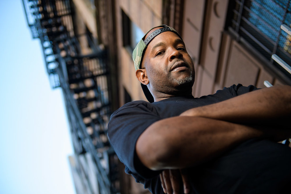 NYC Branded Lifestyle Portrait Podcaster G Moody fire escape looking serious into camera