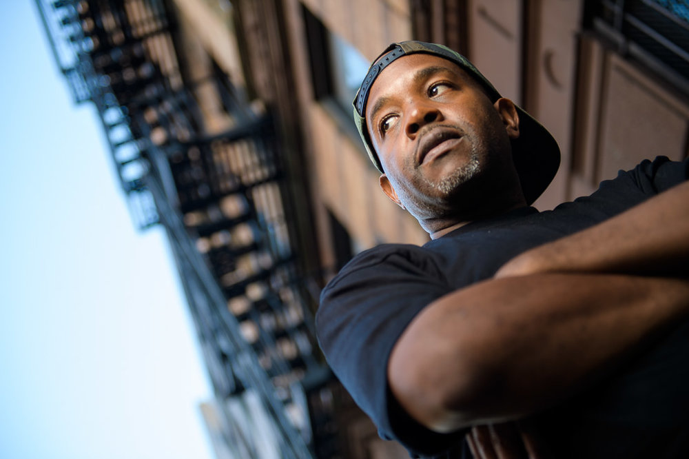 NYC Branded Lifestyle Portrait Podcaster G Moody fire escape looking serious off camera