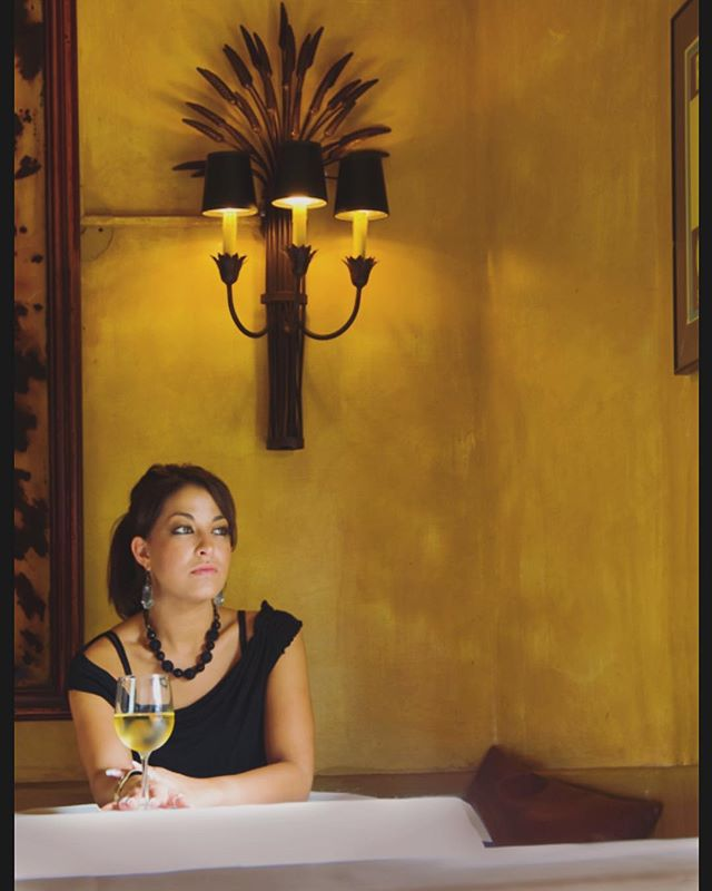 """From the project """"Beautiful Thirst: a Photographer's Journey through Wine Country,"""" a Healdsburg Beauty enjoys a sip before the dining room fills with imbibers. This is the land of the all-day invitation to partake in the grape 🍇 (2005) . . . . . #wine #winelover #winetasting #winecountry #napa #healdsburg #brunette #model #sconce #restaurantdesign #design #light #imbibe #instatravel #travel #photographer #photography #travelphotography"""