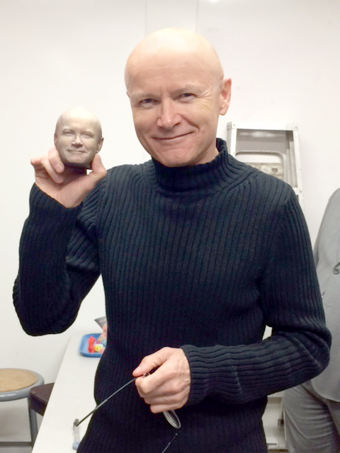 AssentWorks' Robert Elms holds up a miniature version of his own head created on one of seven 3D printers on the premises