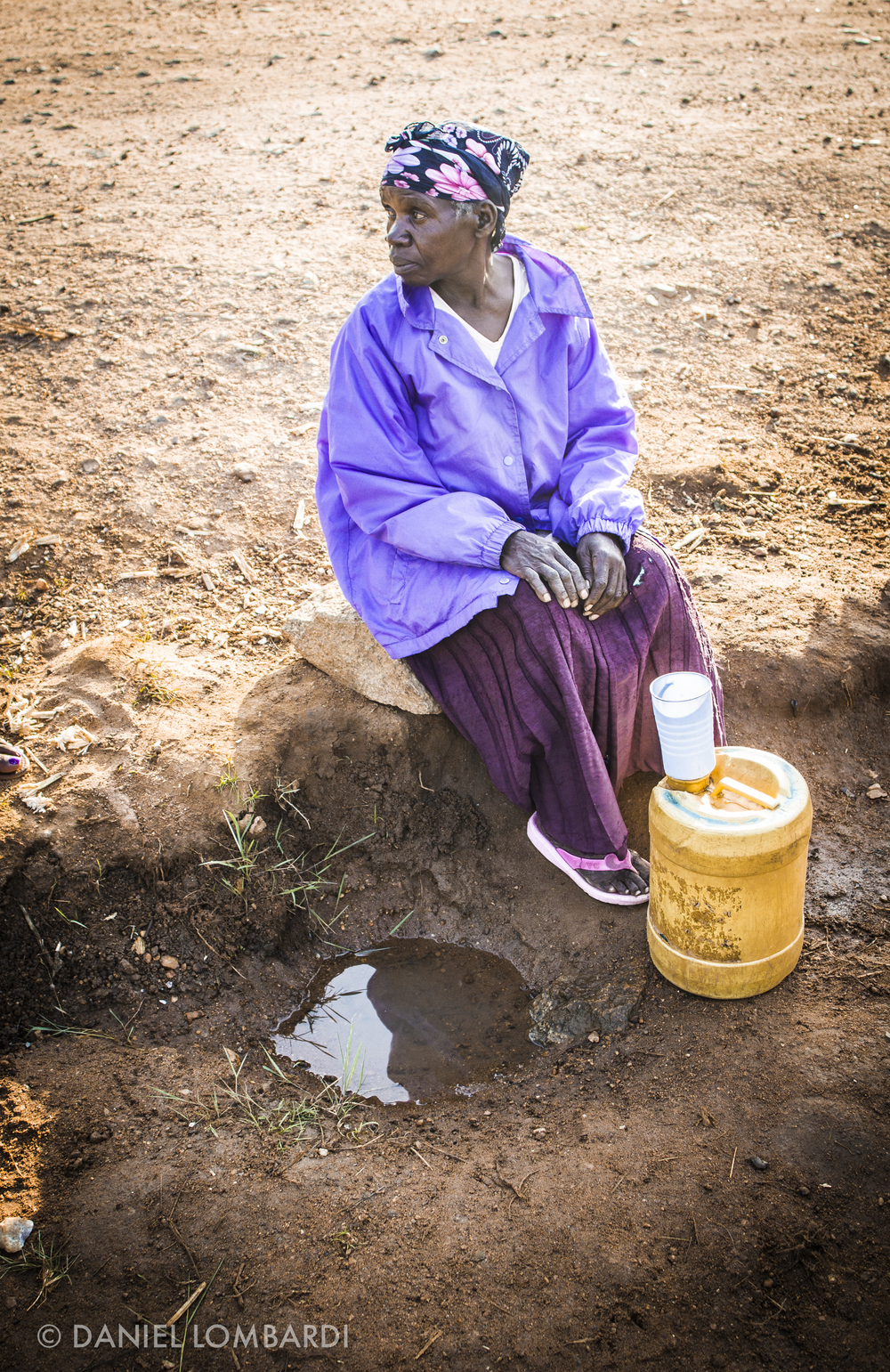 Far more water is swirled away with every flush of the toilet than is available at this watering hole. Cup by cup, Neta Bwonya, of Bisunu Village, provides a day's worth of water for her family. She will treat the water with chlorine and then use it for drinking, cooking, and cleaning.