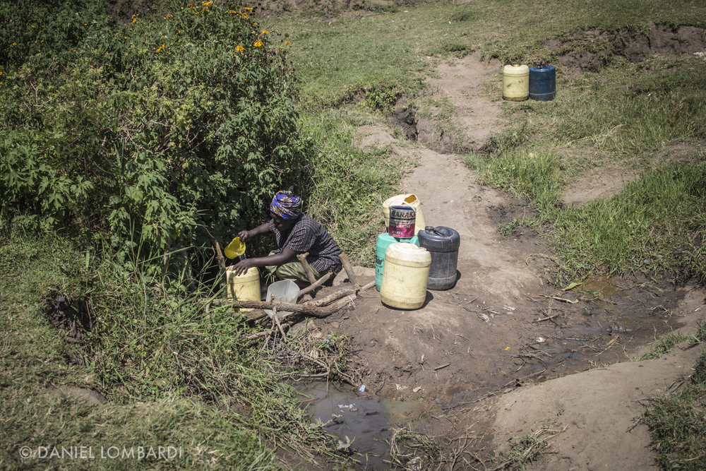 A blind woman collects water from a very popular water collection points in the area. Women who gather water here do their best to scoop water from underneath the bush were the animals don't step in it as much.