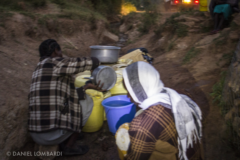 Here women scoop water from the ditch on the side of a dirt road just before sunrise. Some of them had been waiting for their turn for several hours when I took this picture.