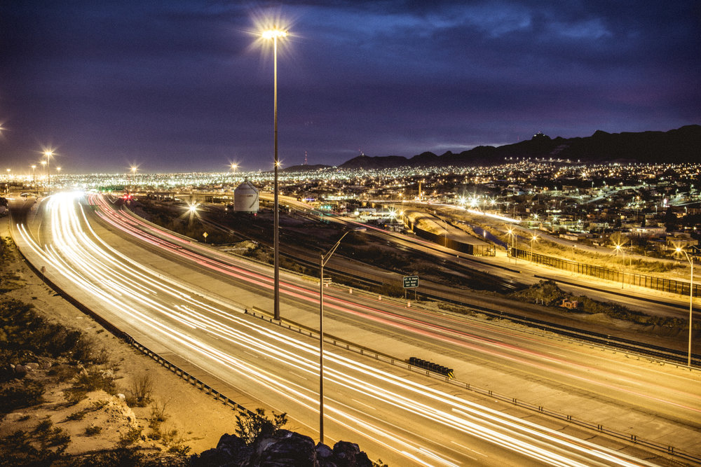 Cars whip down Interstate 10 in El Paso, just north of the border fence, the unhurried Rio Grande and Juarez, Mexico.