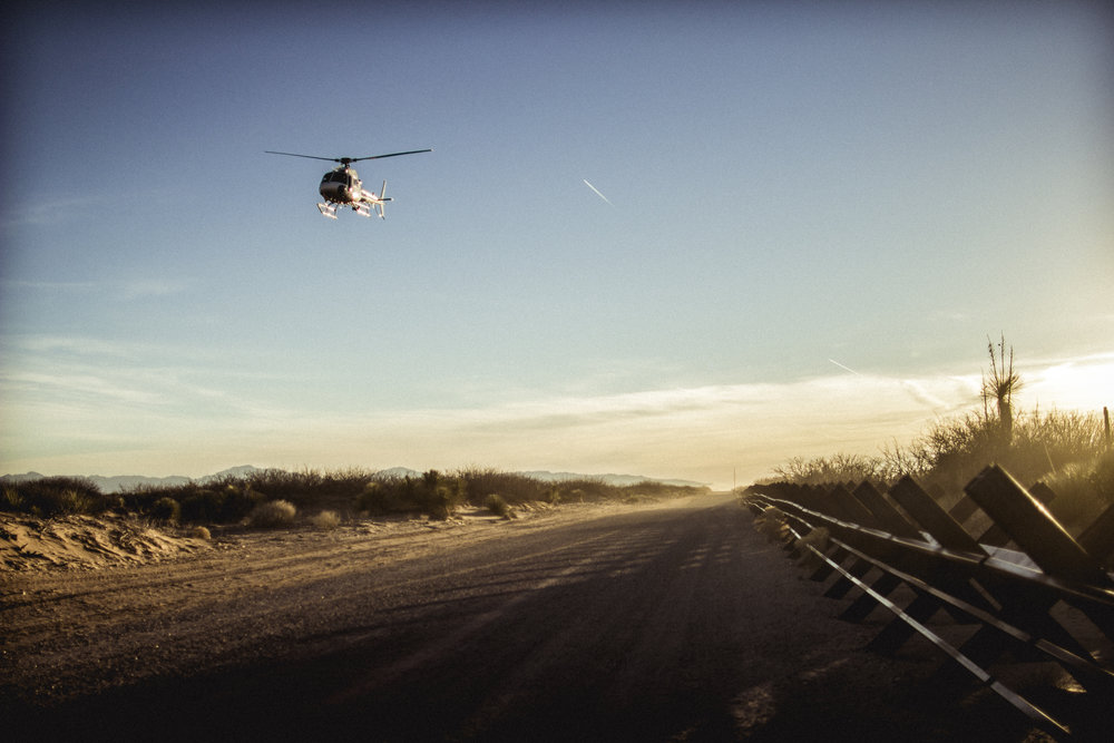 Anti-vehicle fencing made from thick steel cuts through the Chihuahua Desert in New Mexico as a border patrol helicopter roars overhead.