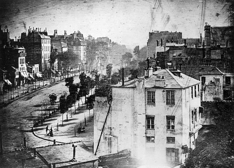 Louis-Jacques-Mandé Daguerre (1787-1851), a romantic painter and printmaker, invented the Daguerreotype, a one of a kind highly detailed image on a polished, silver-plated sheet of copper. Working with Niépce, he created a way to fix the image on metal. His invention became a huge success in Europe and America. Unfortunately, less than 25% of Daguerre's original photographs survived a devastating fire to his laboratory in March of 1839. This image (1938), includes the first known candid photo of a person (lower left).
