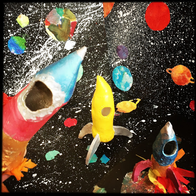 Clay spaceships photographed in front of our solar system paintings