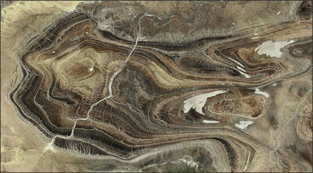 An amazing area to check out. The drainage ignores...but not entirely...some elaborate folds in the desert.    http://www.flashearth.com/?lat=25.404948&lon=1.769611&z=11.4&r=0&src=msa