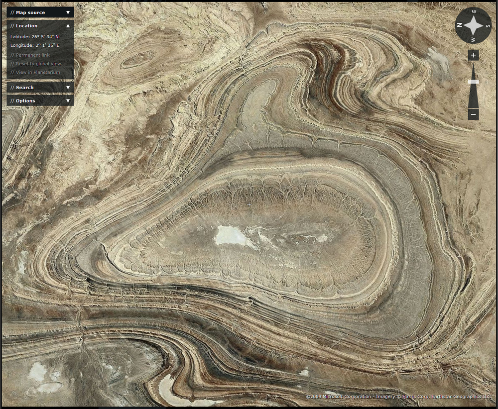 The Algerian Tanezrouft ('Land of Terror') Basin is a classic area of geopathological geomorphology.  Any part of it produces stunning images.  Japan's ALOS remote image looks like modern art.  Deflation by the wind exposes these shallow periclinal synclinal basins in Palaeozoic rocks. The flashearth image, a good place to start exploring this wonderful place is here.