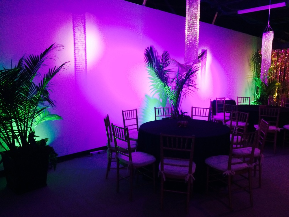 Acrylic crystal chandeliers act as room decor and floating centerpieces. LED uplighting in fuchsia and green added bold color to plain white walls.