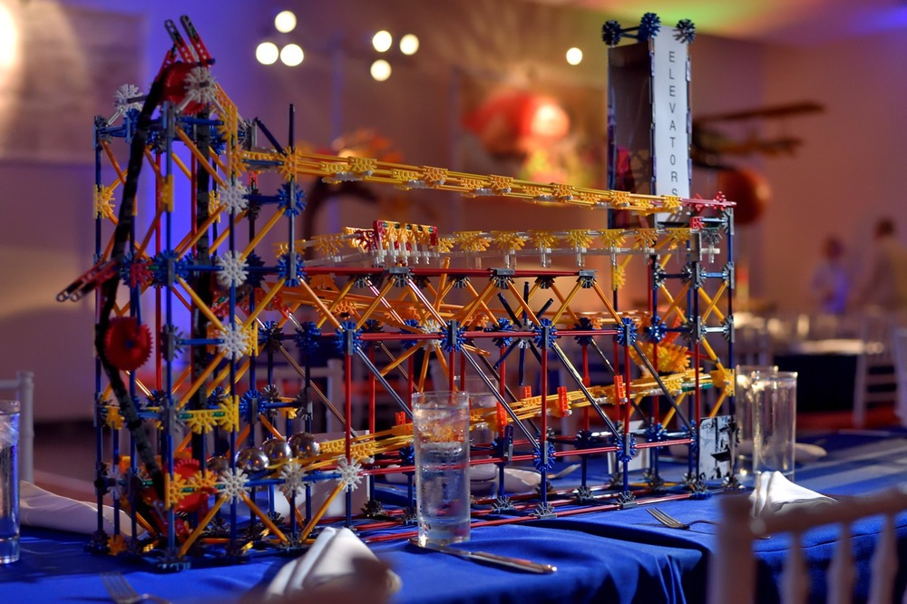 An interactive, kinetic centerpiece with moving parts to represent an elevator. Photography by  Rich Schaub Photography
