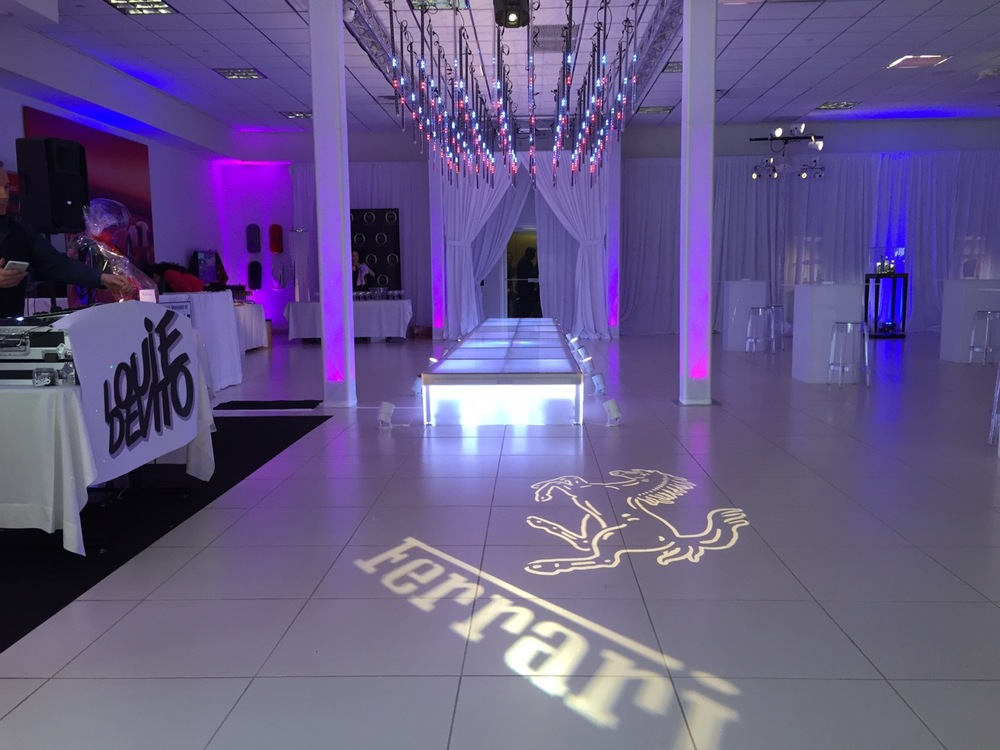 LED light tubes, truss, and custom logo projection provided by Eggsotic Events • Photo by Josh Casto
