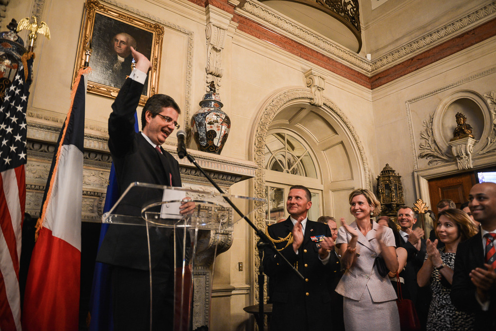 French Ambassador François Delattre says goodbye to a warm-hearted party of well-wishers at his goodbye party in Washington, DC on July 10, with French Defense Attache Brigadier General Bruno Caïtucoli (center) and the Ambassador's wife Sophie (pink) standing by. Guests cheered as the Ambassador gave a light-hearted speech celebrating strong relations between the US and France before bidding adieu (Kate Warren for The Washington Post).