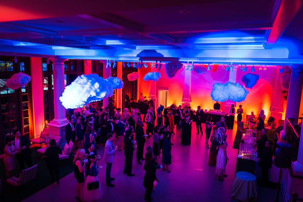 Guests at the surrealism themed Night Nouveau listen to the hosts give remarks amid floating clouds and wild light decorations at the Halcyon House mansion in Georgetown. Previously an enormous artist's studio, the space was bought by Dr. Sachiko Kuno and converted into a social entrepreneurship fellowship program.