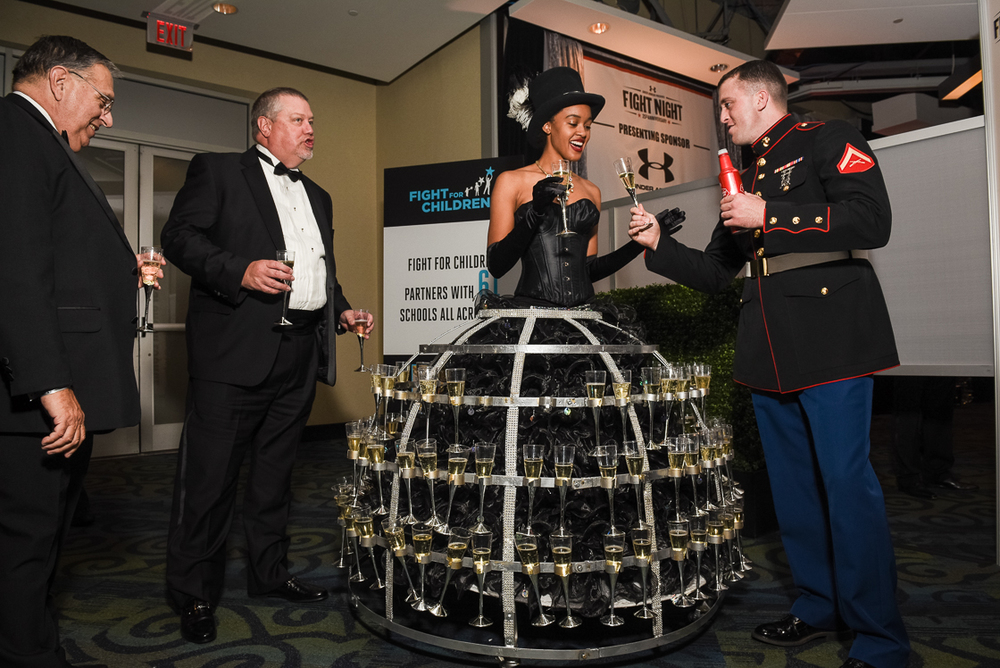 Ensconced in a champagne flute cage, Tina Brown doles out drinks to Lance Corporal Reid Norfolk and other guests during the Fight Night benefit cocktail hour.